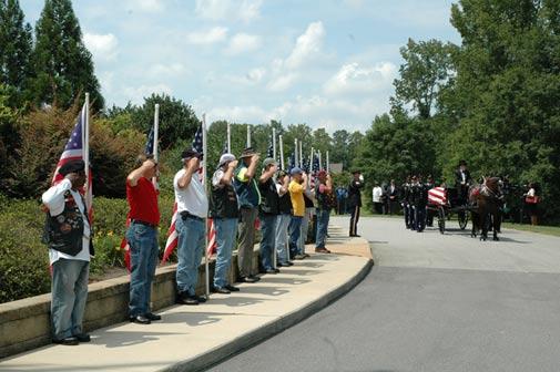 Civilians saluting a fallen soldier