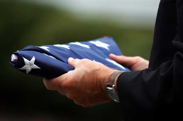 Man holding folded flag