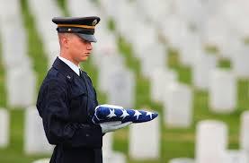 Soldier handing folded flag to family member